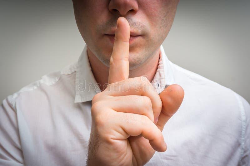 Attraktiver Mann mit dem Finger auf den Lippen, die Ruhegeste machen lizenzfreie stockfotos