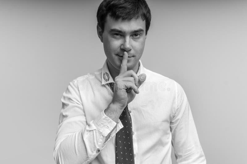 Attraktiver Mann mit dem Finger auf Lippen und Lippenstift am Hemdkragen stockbild
