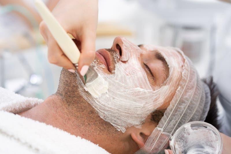 Attraktiver Mann mit der Gesichtscreme, die am Badekurort liegt und sich entspannt lizenzfreies stockfoto