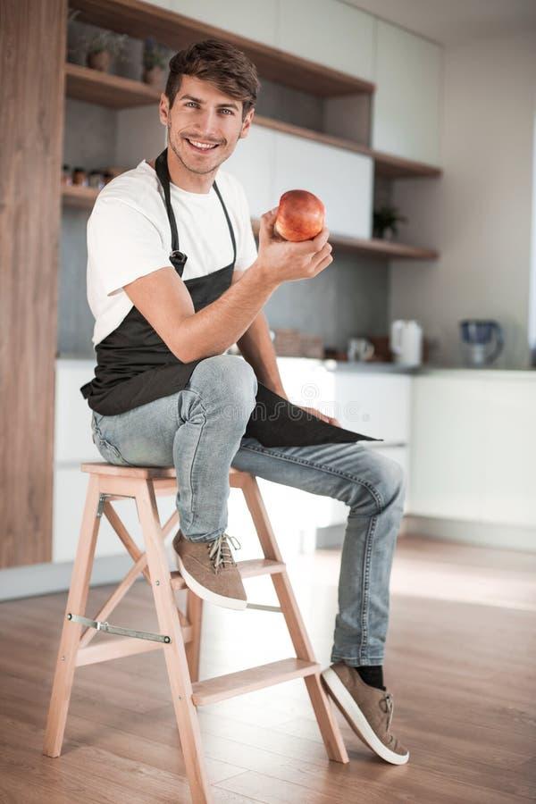 Attraktiver Mann mit einem Apfel, der in einer Hauptküche sitzt lizenzfreies stockfoto