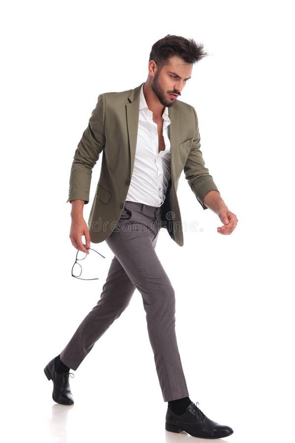 Attraktiver Mann mit grüner Klage gehend mit Seiten versehen lizenzfreies stockfoto