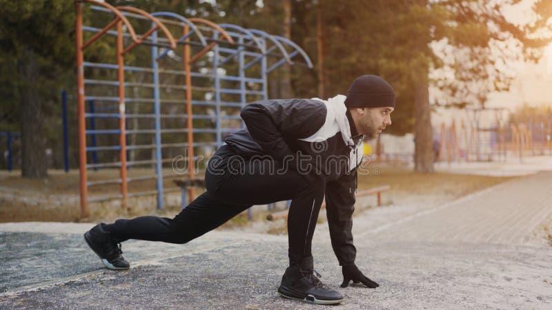 Attraktiver Mannläufer, der die Übung ausdehnend sich vorbereitet für Morgengymnastik und rüttelt im Winterpark tut lizenzfreies stockfoto
