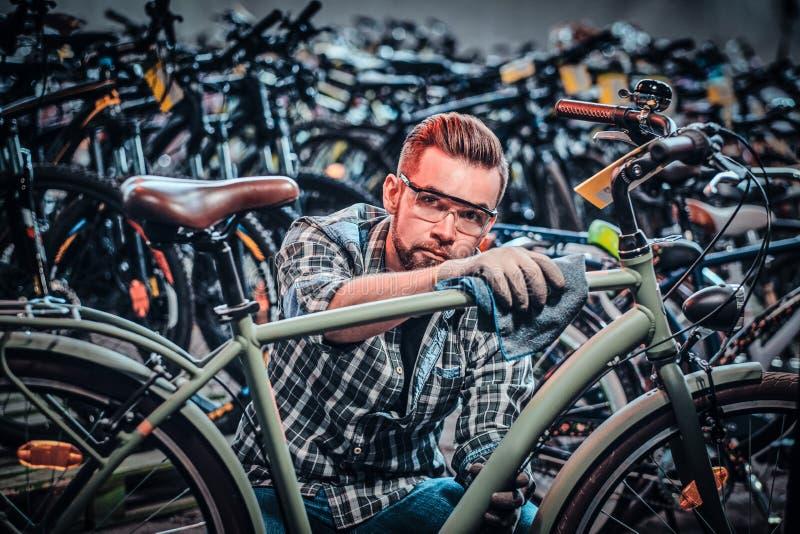 Attraktiver nachdenklicher Mann in den Schutzgläsern säubert Fahrrad an seinem eigenen Geschäft lizenzfreie stockbilder