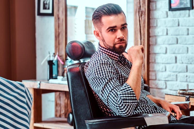 Attraktiver nachdenklicher Mann wartet auf seine Drehung, um einen Haarschnitt am beschäftigten Friseursalon zu erhalten lizenzfreies stockfoto
