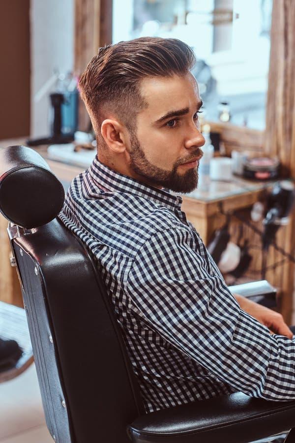 Attraktiver nachdenklicher Mann wartet auf seine Drehung, um einen Haarschnitt am besch?ftigten Friseursalon zu erhalten lizenzfreies stockbild