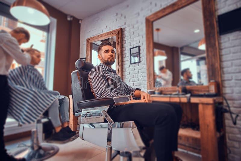 Attraktiver nachdenklicher Mann wartet auf seine Drehung, um einen Haarschnitt am besch?ftigten Friseursalon zu erhalten lizenzfreie stockbilder