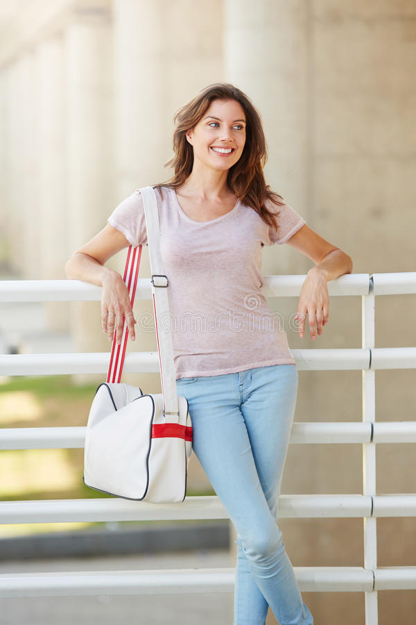 Attraktiver Reisender der jungen Frau, der mit Tasche lächelt lizenzfreie stockbilder