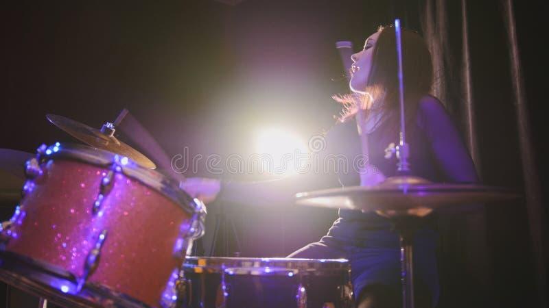 Attraktiver Rockmusiker des jungen Mädchens - weibliche Schlagzeugerausführung lizenzfreie stockbilder