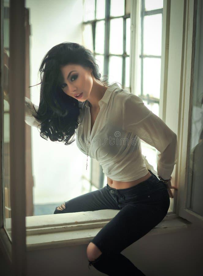 Attraktiver sexy Brunette im weißen festen Sitzhemd und -SCHWARZEM zerriss die Jeans, die das Sitzen auf Fensterrahmen aufwerfen  lizenzfreies stockfoto