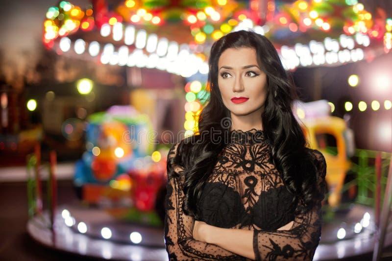 Attraktiver sexy Brunette mit der schwarzen Spitzebluse, die draußen mit Karussell in Hintergrund aufwirft Porträt der sinnlichen stockfotografie