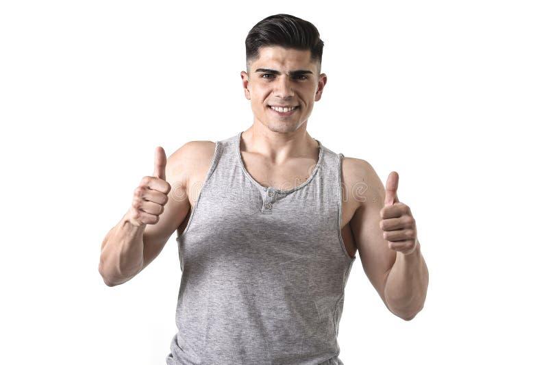 Attraktiver Sportmann mit dem lächelnden glücklichen tragenden Unterhemd des großen und starken athletischen Körpers, das Daumen  stockbilder