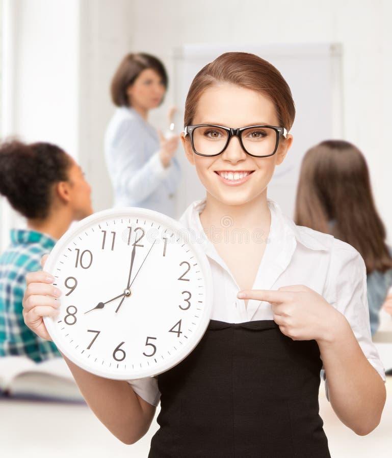 Attraktiver Student, der auf Uhr zeigt lizenzfreies stockbild