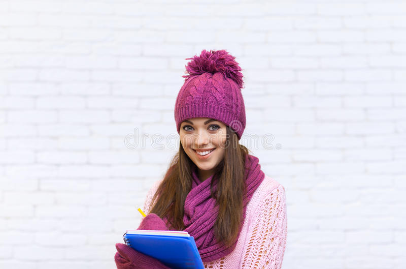 Attraktiver Student Smile Teenage Girl im rosa Hut, der Ordner-Bleistift hält stockfoto