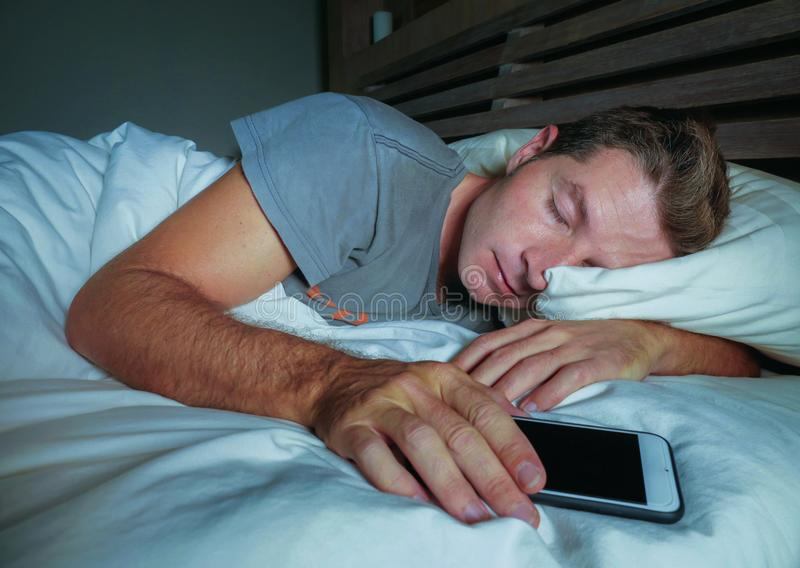 Attraktiver und hübscher müder Mann auf seinem 30s oder 40s im Bett friedlich schlafend und entspannt nachts Handy im Internierte stockbild