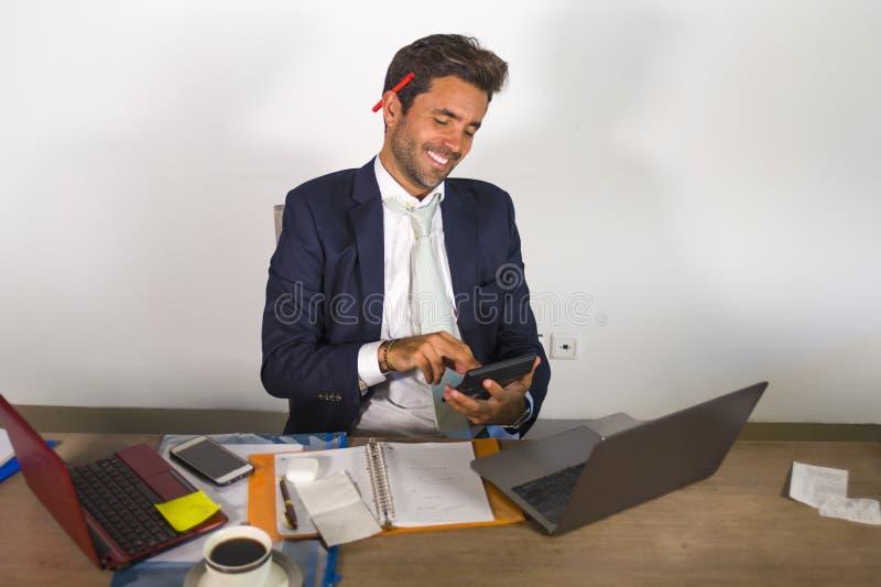 Attraktiver und leistungsfähiger Geschäftsmann, der am Bürolaptopcomputertisch überzeugt beim Lächeln glücklich unter Verwendung  stockfotos