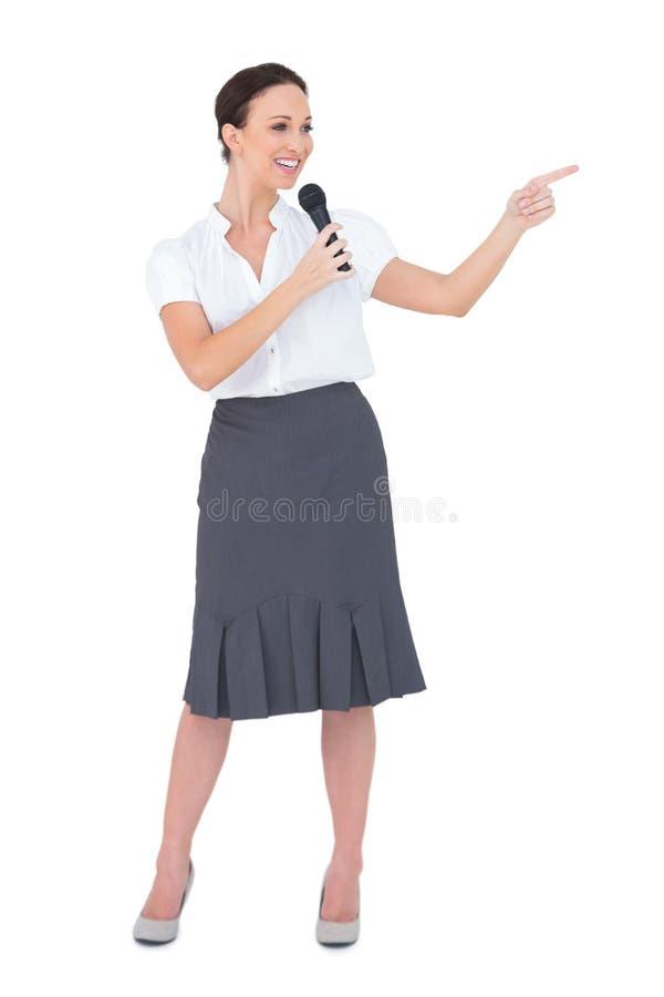 Attraktiver Vorführer, der das Mikrofonzeigen hält stockbild