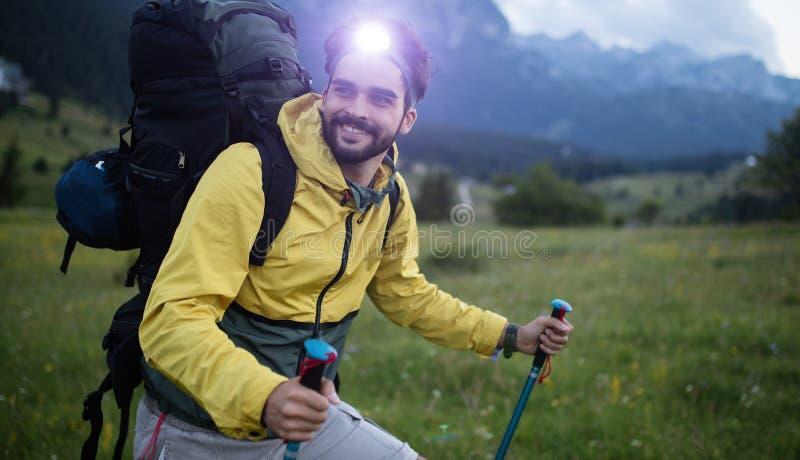 Attraktiver Wanderer mit dem gro?en reisenden Rucksack, der sich oben auf dem Gebirgspfad und dem L?cheln verschiebt lizenzfreies stockfoto