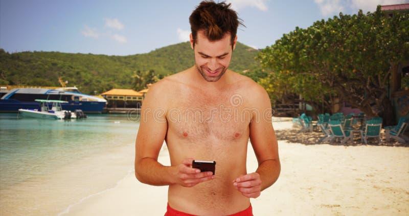 Attraktiver weißer Kerl an einem Erholungsort unter Verwendung der Datierung von APP an seinem Telefon lizenzfreie stockbilder