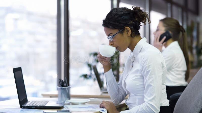 Attraktiver weiblicher Büroangestellttrinkbecher Kaffee- und Lesediagramme lizenzfreies stockbild