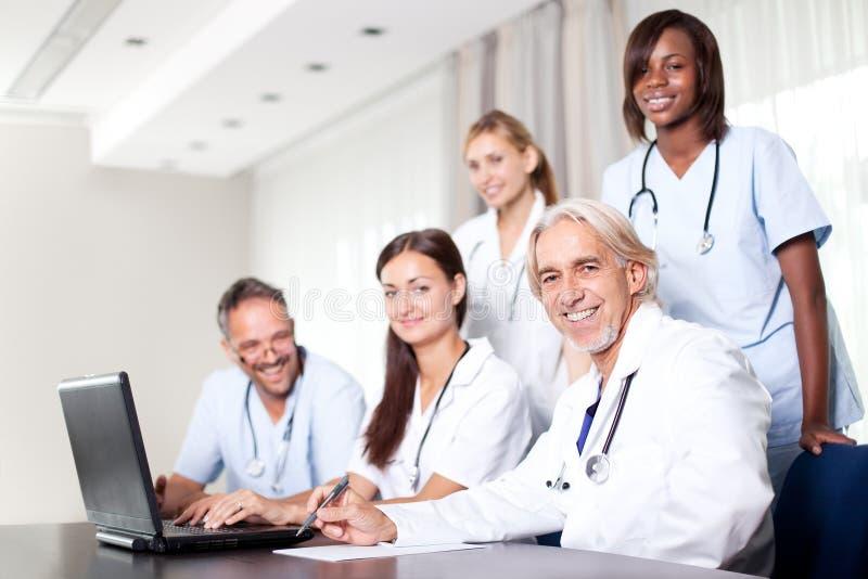Attraktiver weiblicher Doktor, der an ihrem Laptop arbeitet lizenzfreies stockfoto