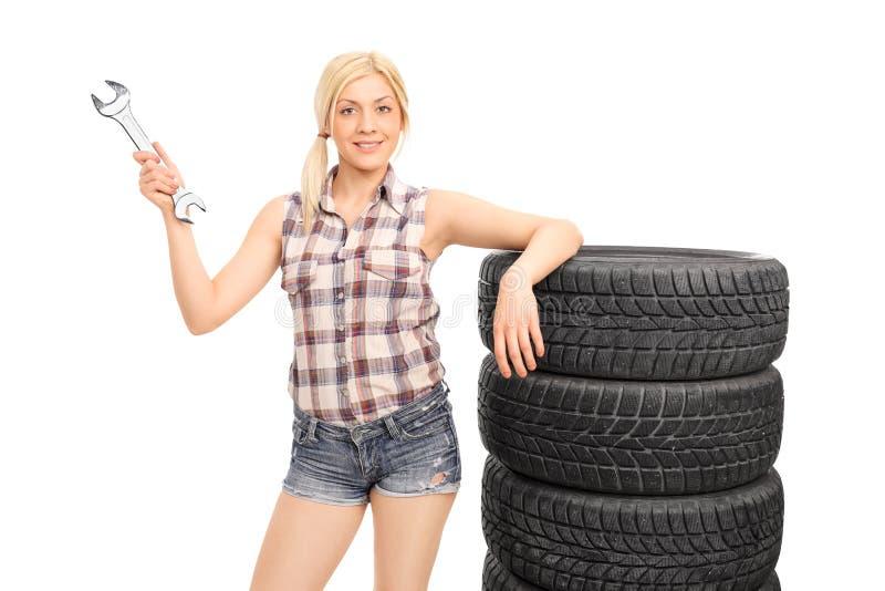 Attraktiver weiblicher Mechaniker, der einen enormen Schlüssel hält stockfoto