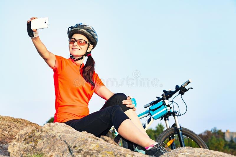 Attraktiver weiblicher Radfahrer, der ein selfie Foto im Freien macht lizenzfreie stockfotografie