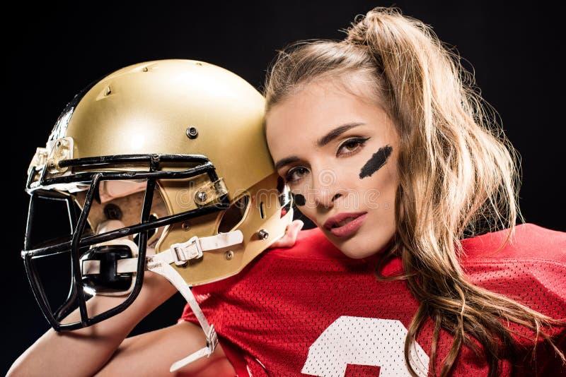 Attraktiver weiblicher Spieler des amerikanischen Fußballs in der Uniform, die mit Sturzhelm und dem Schauen aufwirft stockfoto