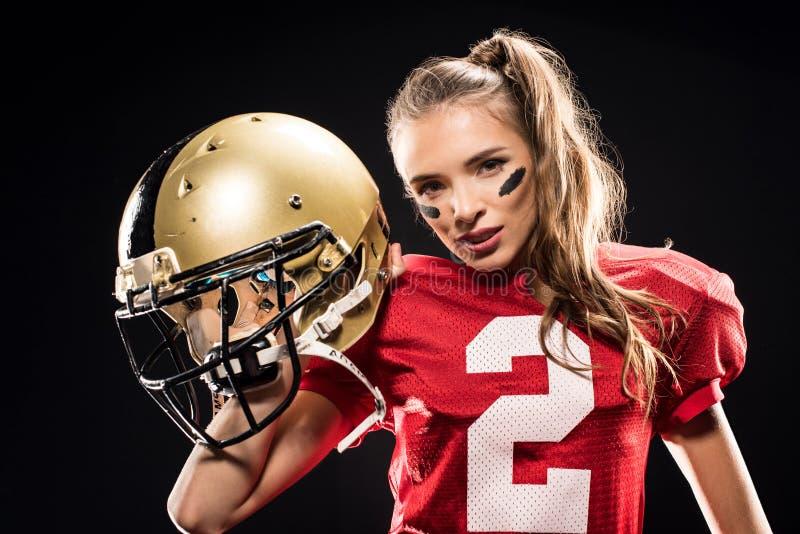 Attraktiver weiblicher Spieler des amerikanischen Fußballs in der Uniform, die mit Sturzhelm und dem Schauen aufwirft stockbild