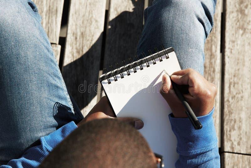 Attraktiver zufällig gekleideter junger schwarzer männlicher Student, der Anmerkungen im Schreibheft, bereitend für Lektion an de lizenzfreies stockfoto