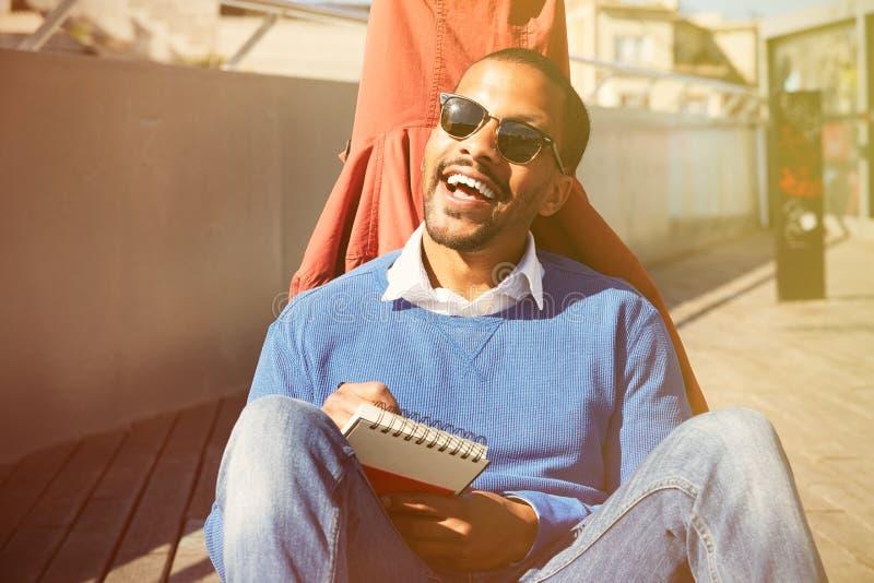 Attraktiver zufällig gekleideter junger schwarzer männlicher Student mit der Sonnenbrille, die Anmerkungen im Schreibheft, bereit stockfoto