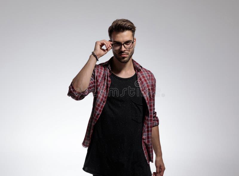 Attraktiver zufälliger Mann, der seine Gläser repariert stockbilder