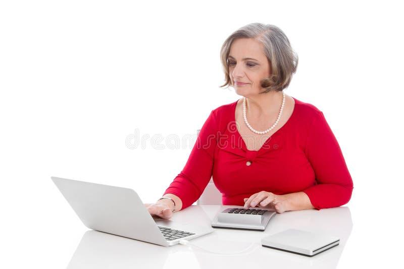 Attraktives älteres weibliches Krippensitzen lokalisiert auf Schreibtisch mit Co stockbild
