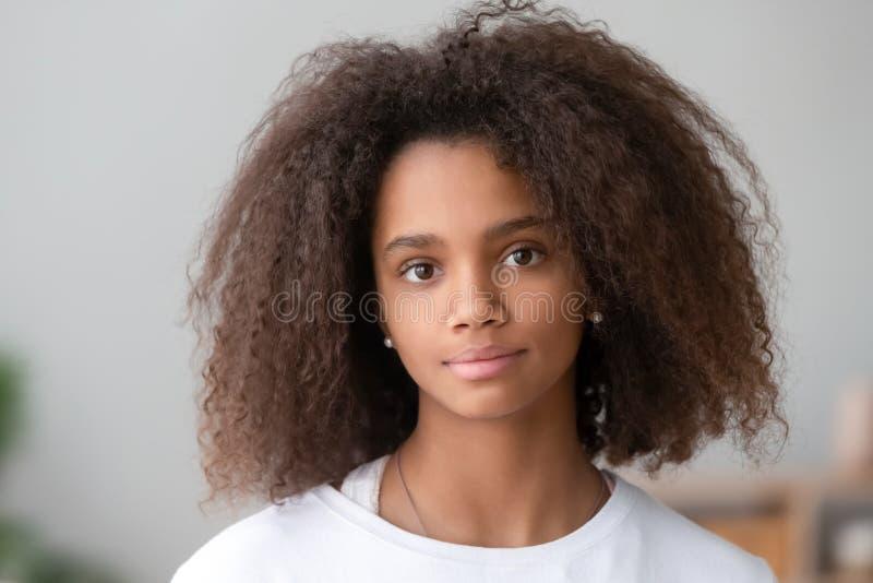 Attraktives afrikanisches Jugendlichmädchen des Hauptschussporträts, das Kamera betrachtet stockbild
