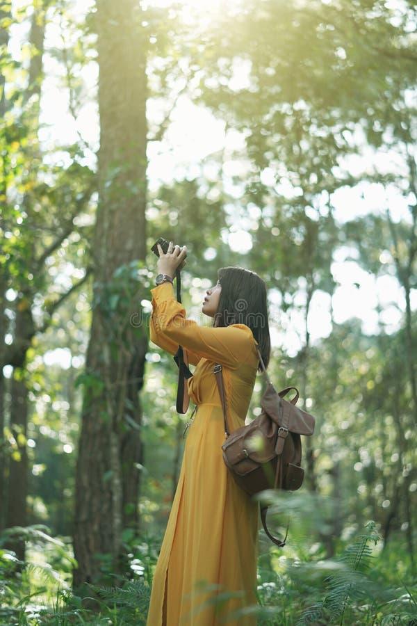 Attraktives Asiatinabenteuer, in der natürlichen Waldbesichtigung und mit Kamera, machen ein Foto an der Urlaubsreise lizenzfreies stockfoto