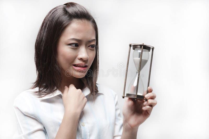 Attraktives asiatisches Geschäftsfrauholding-Stundenglas lizenzfreies stockbild
