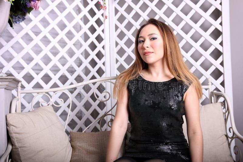 Attraktives asiatisches Mädchen, das auf der Couch sitzt und die Kamera betrachtet stockfoto