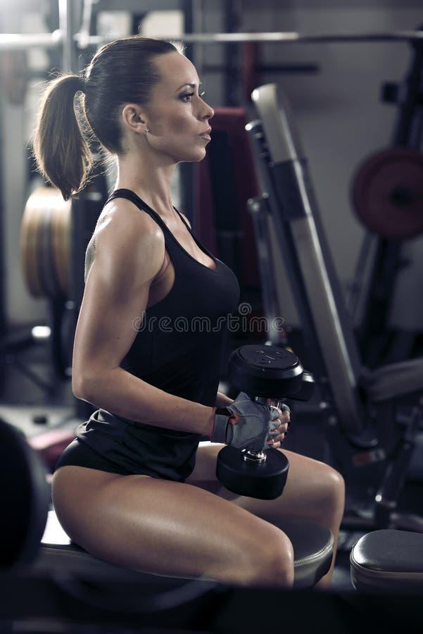 Attraktives athletisches Mädchen, das Bizeps auf einem dunklen Hintergrund macht stockbilder