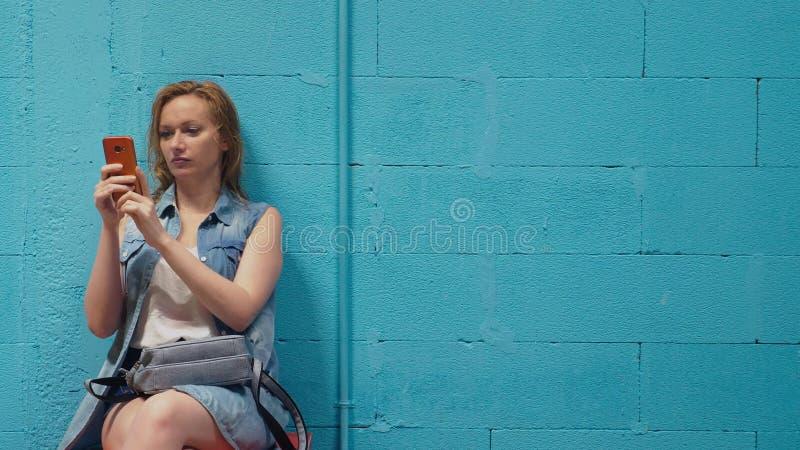 Attraktives blondes Mädchen benutzt roten Smartphone gegen eine blaue Wand stockfotos