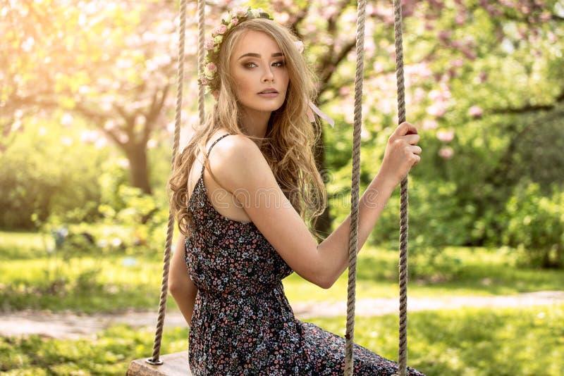 Attraktives blondes Mädchen in blühendem Garten lizenzfreie stockbilder