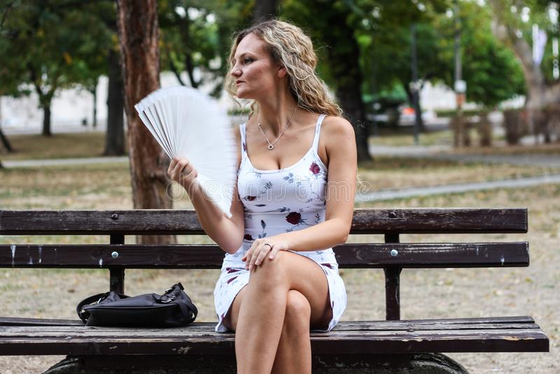 Attraktives blondes Mädchen, das auf der Bank in einem Park und in einem Coolin sitzt stockfoto