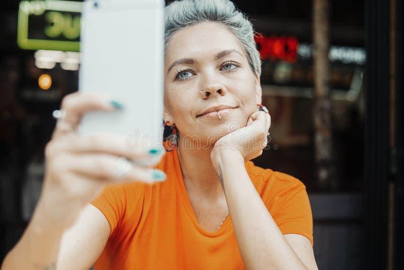 Attraktives blondes Mädchen, das selfie am Café macht und Kaffee trinkt stockbilder