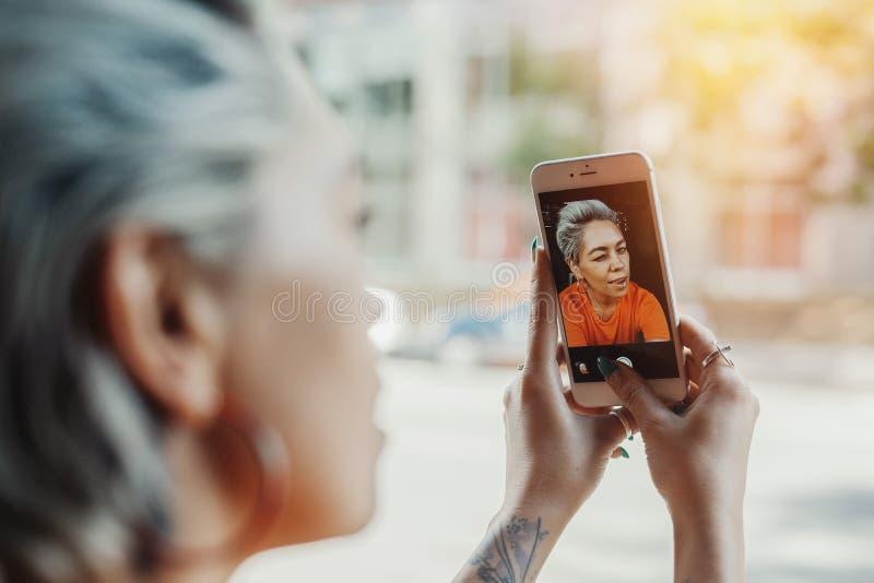 Attraktives blondes Mädchen, das selfie am Café macht und Kaffee trinkt lizenzfreie stockfotografie