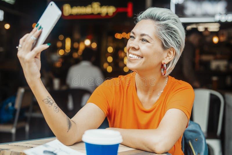 Attraktives blondes Mädchen, das selfie am Café macht und Kaffee trinkt stockfotografie