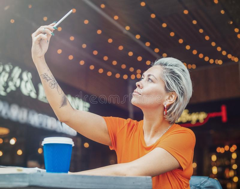 Attraktives blondes Mädchen, das selfie am Café macht und Kaffee trinkt stockbild