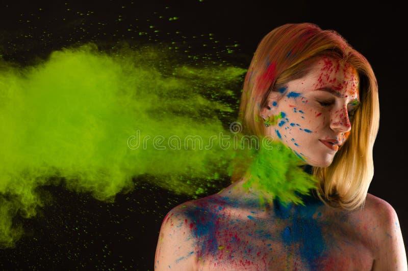 Attraktives blondes Mädchen in den Farben Holi stockfotografie