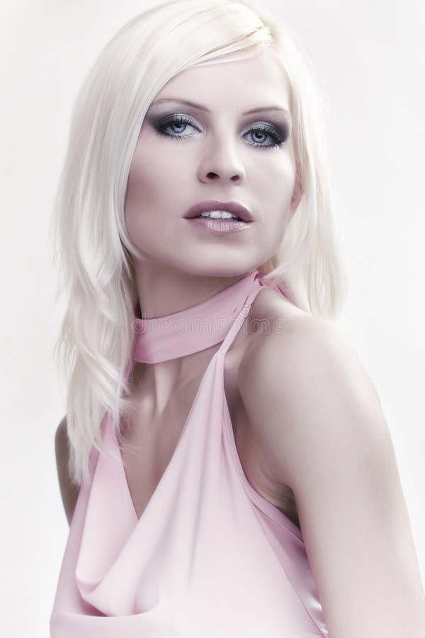 Attraktives blondes Mädchen des Portraits im Rosa stockbild
