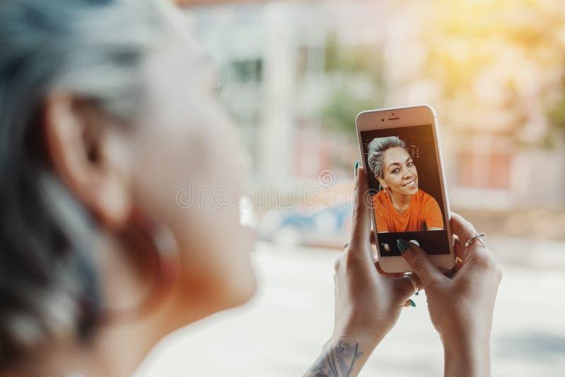Attraktives blondes Mädchen im orange T-Shirt, das selfie am Café durch ihr Telefon macht stockfotos