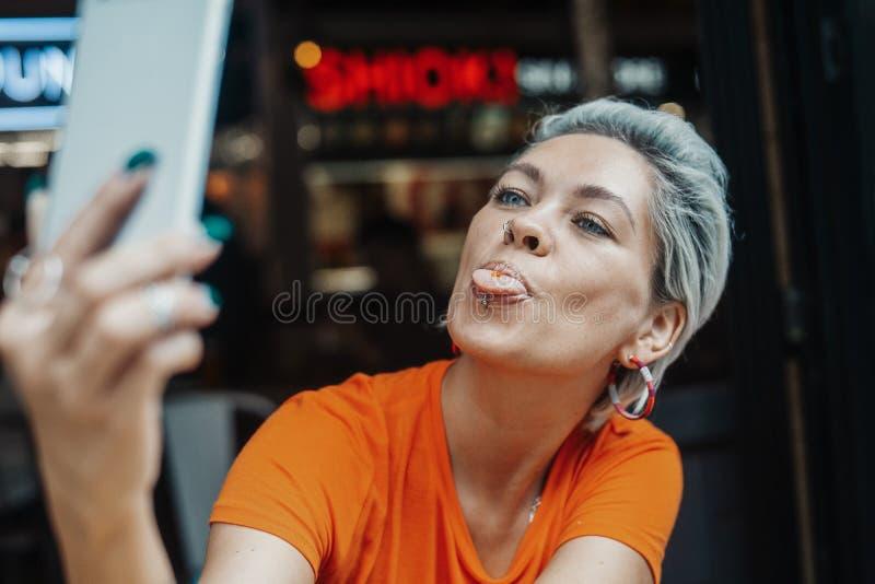 Attraktives blondes Mädchen im orange T-Shirt, das selfie am Café macht stockbild