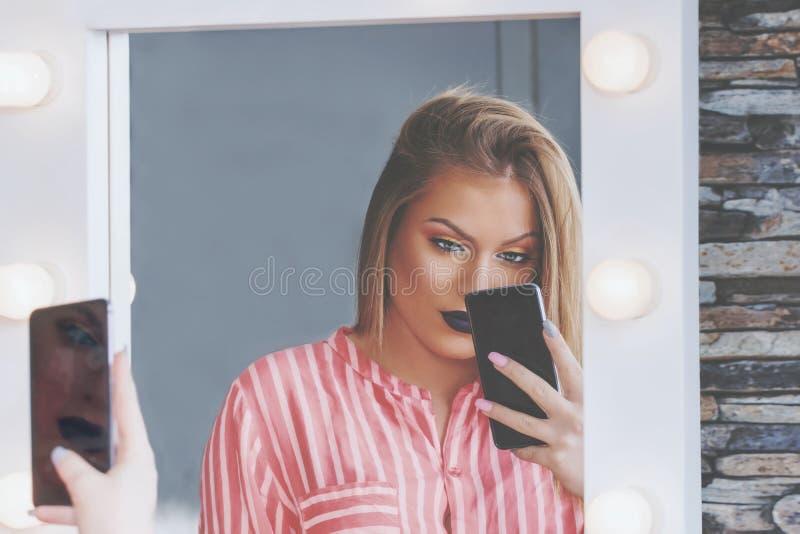 Attraktives blondes Mädchen macht selfie im Schminkspiegel mit Lampen lizenzfreie stockfotografie