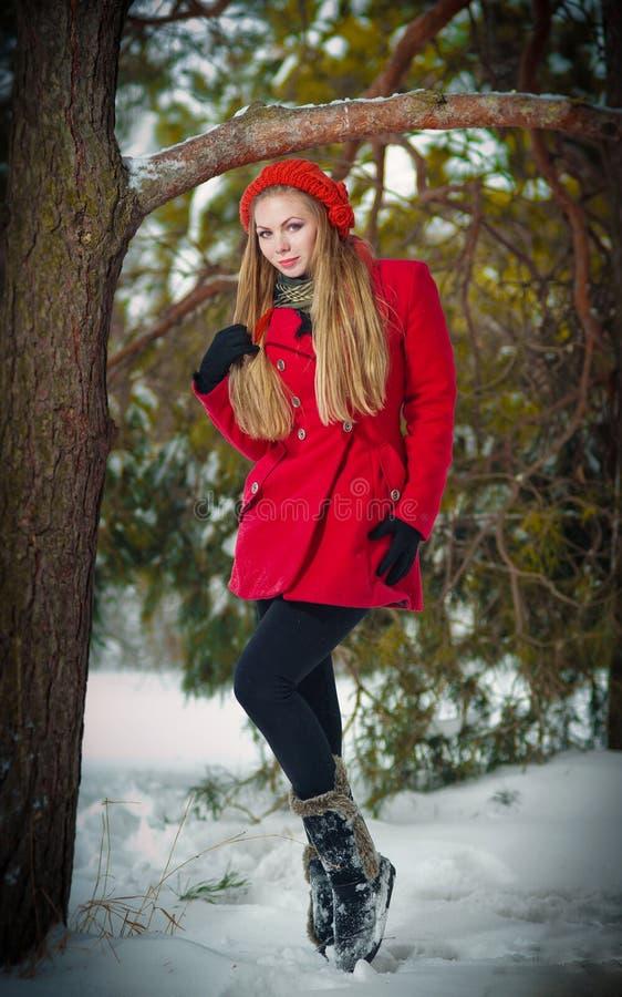 Attraktives blondes Mädchen mit Handschuhen, roter Mantel und rote der Hut, die Winter aufwirft, schneien. Schönheitsfrau in der W lizenzfreie stockbilder